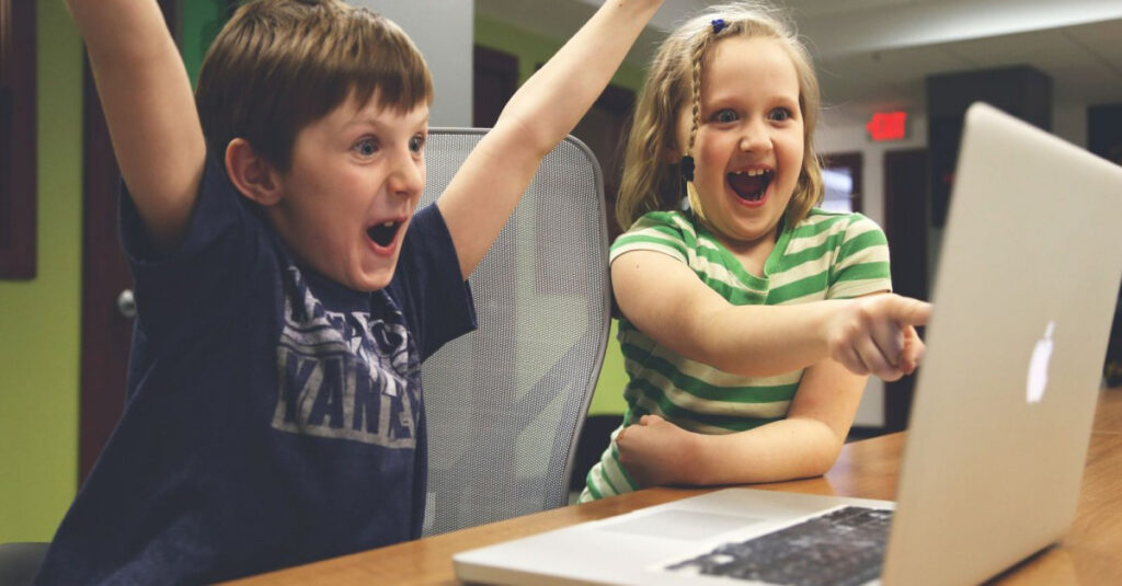 two kids pointing at a computer