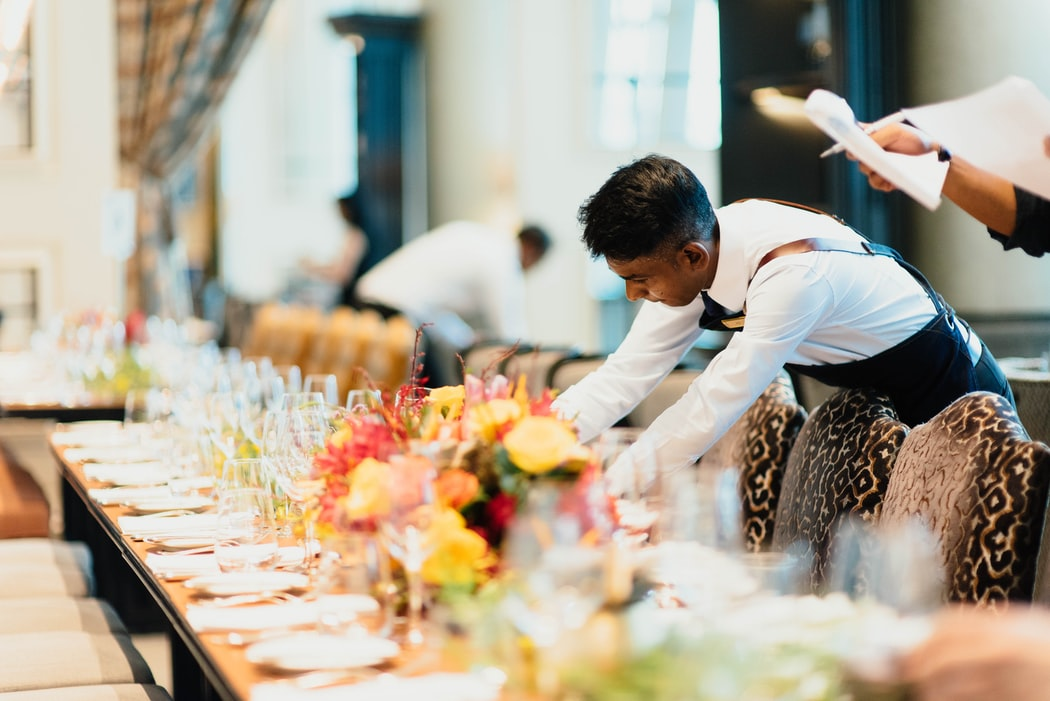 man setting the table for guests