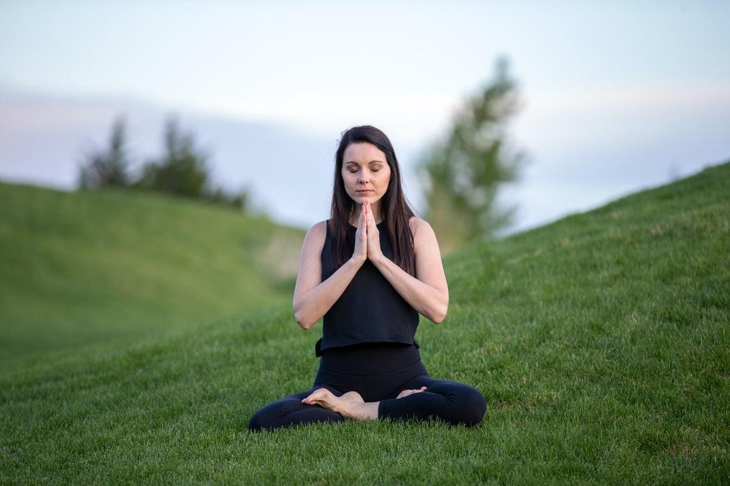 a women meditating on grass